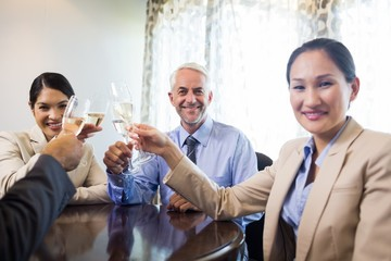 Portrait of business colleagues toasting wine glasses
