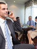 Businessman using cellphone with colleagues having meal