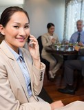 Businesswoman using cellphone with colleagues having meal