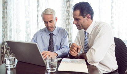 Businessmen using laptop at office desk