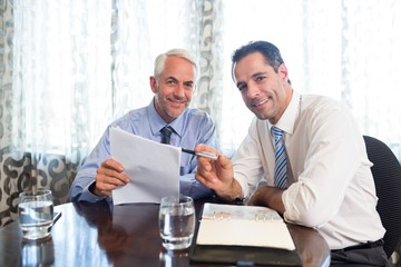 Businessmen doing paperwork at desk