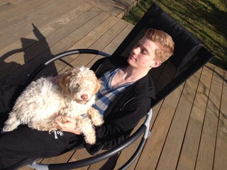 Teenager mit Hund auf Liegestuhl