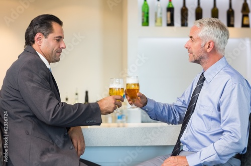 Business colleagues toasting beer glasses at bar counter