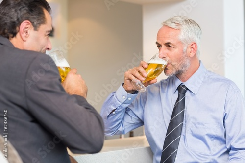 Business colleagues drinking beer at bar counter
