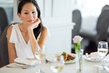 Beautiful smiling young woman at meal table