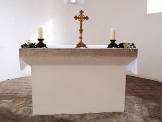 Schlichter Altar mit Kreuz in einer alten Kirche