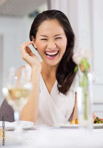 Portrait of a laughing woman at meal table