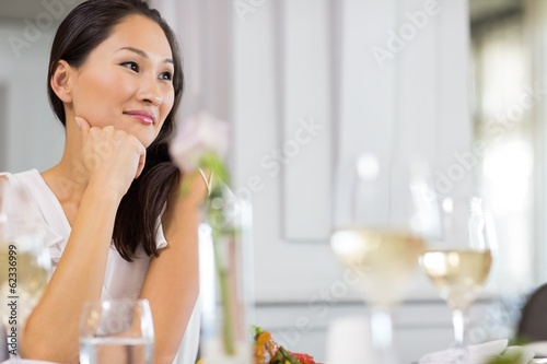 Thoughtful beautiful woman at meal table