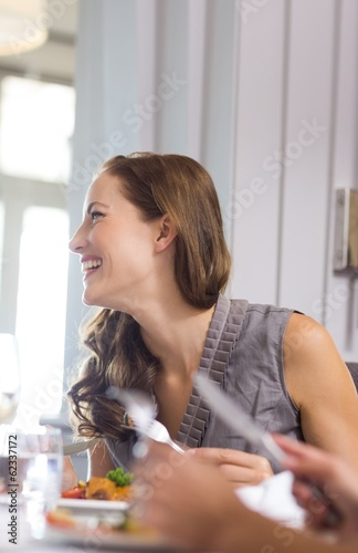 Beautiful smiling woman having food with friend at restaurant