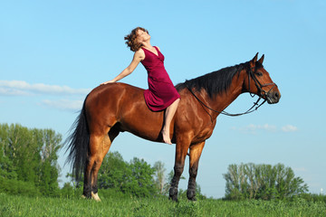 Girl riding on back of a German pony in a meadow