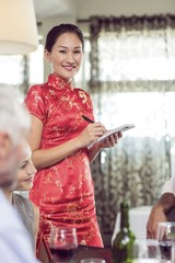 Portrait of smiling waitress with people at dining table in
