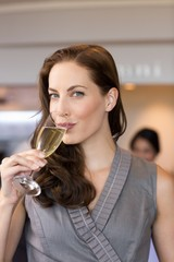 Businesswoman drinking champagne with colleagues in background