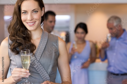 Businesswoman holding champagne flute with colleagues in