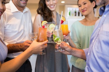 Mid section of cheerful people toasting cocktails