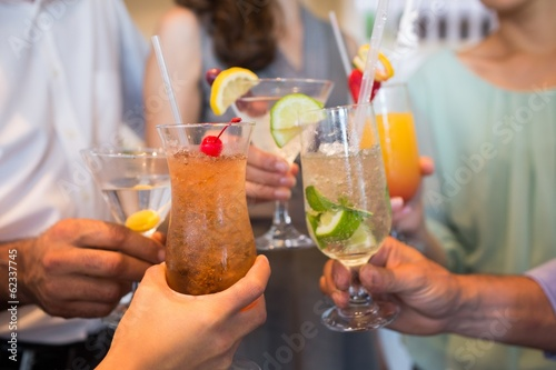 Closeup mid section of people toasting cocktails