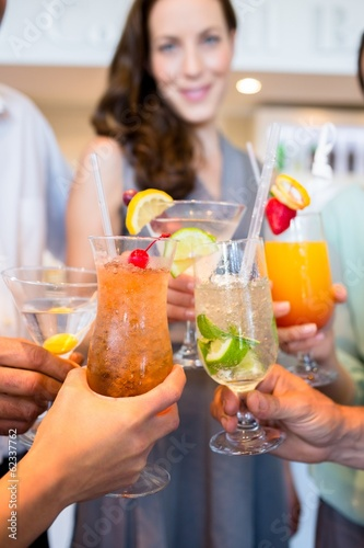 Closeup of cheerful people toasting cocktails