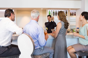 People with cocktail glasses looking at bartender prepare a drin
