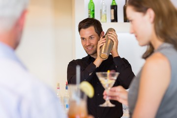 People with cocktail glasses looking at the bartender prepare