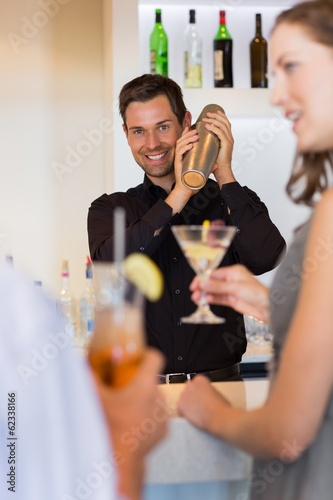People with cocktail glasses looking at the bartender prepare a