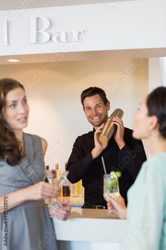People holding cocktail glasses with bartender preparing a drink