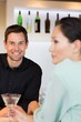 Smiling bartender with a woman at bar counter