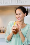 Smiling young woman holding cocktail glass at the bar