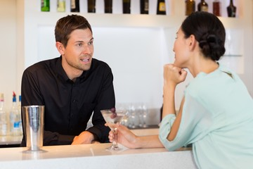 Woman talking to bartender at the bar counter