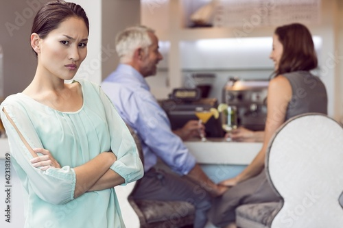 Angry woman with couple toasting cocktails in background