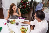Man giving gift box to smiling woman in restaurant