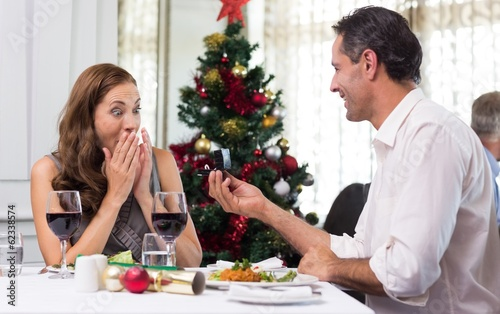 Man proposing a surprised woman in the restaurant