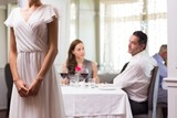 Woman standing with couple dining in restaurant