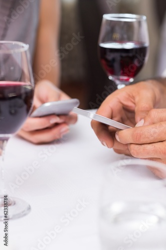 Mid section of a couple with wine glass text messaging