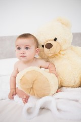 Baby boy with teddy bear in bed