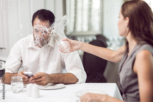 Woman throwing water on man in restaurant