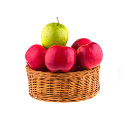 Fresh red and one green apples in a wooden basket