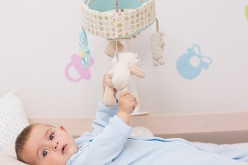 Baby boy playing with toys in crib