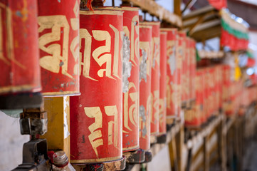 Old buddhist prayer wheels with Tibetan prayer inscription