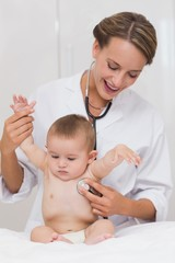 Female doctor checking baby