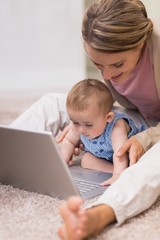 Beautiful mother teaching baby to use laptop