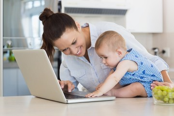 Mother and baby using laptop at counter