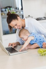 Mother with baby using laptop at counter