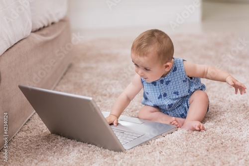 Cute baby boy using laptop