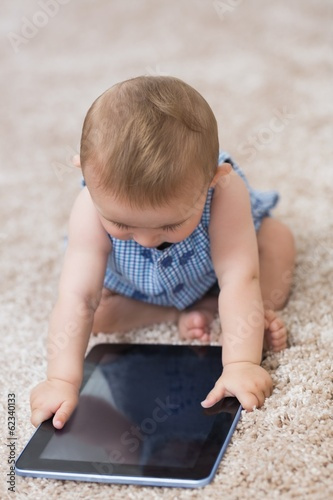 Baby boy playing with digital tablet at home