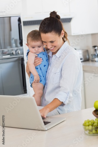 Mother using laptop while carrying baby at counter