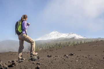 young woman on top of a mountain enjoying the view of volcano te
