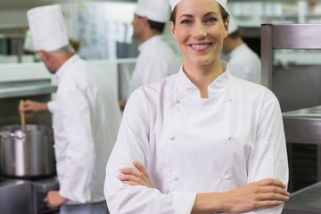 Smiling chef looking at camera with team working behind
