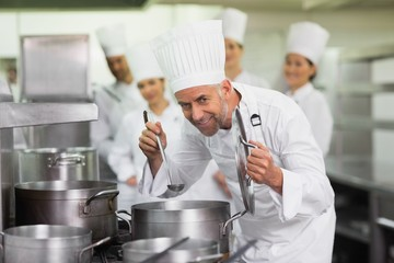 Head chef smelling pot of soup and smiling at camera