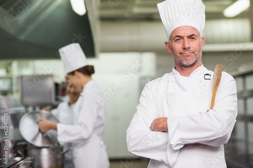 Head chef looking at camera holding wooden spoon