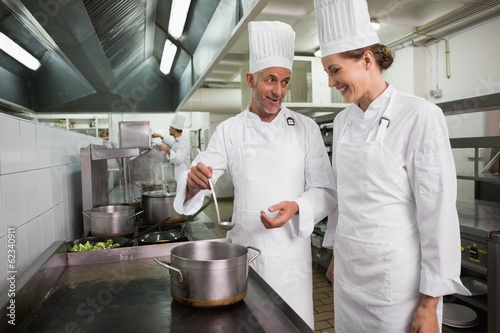 Two happy chefs chatting over a large pot at the stove