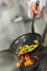 Chef frying vegetables in a wok